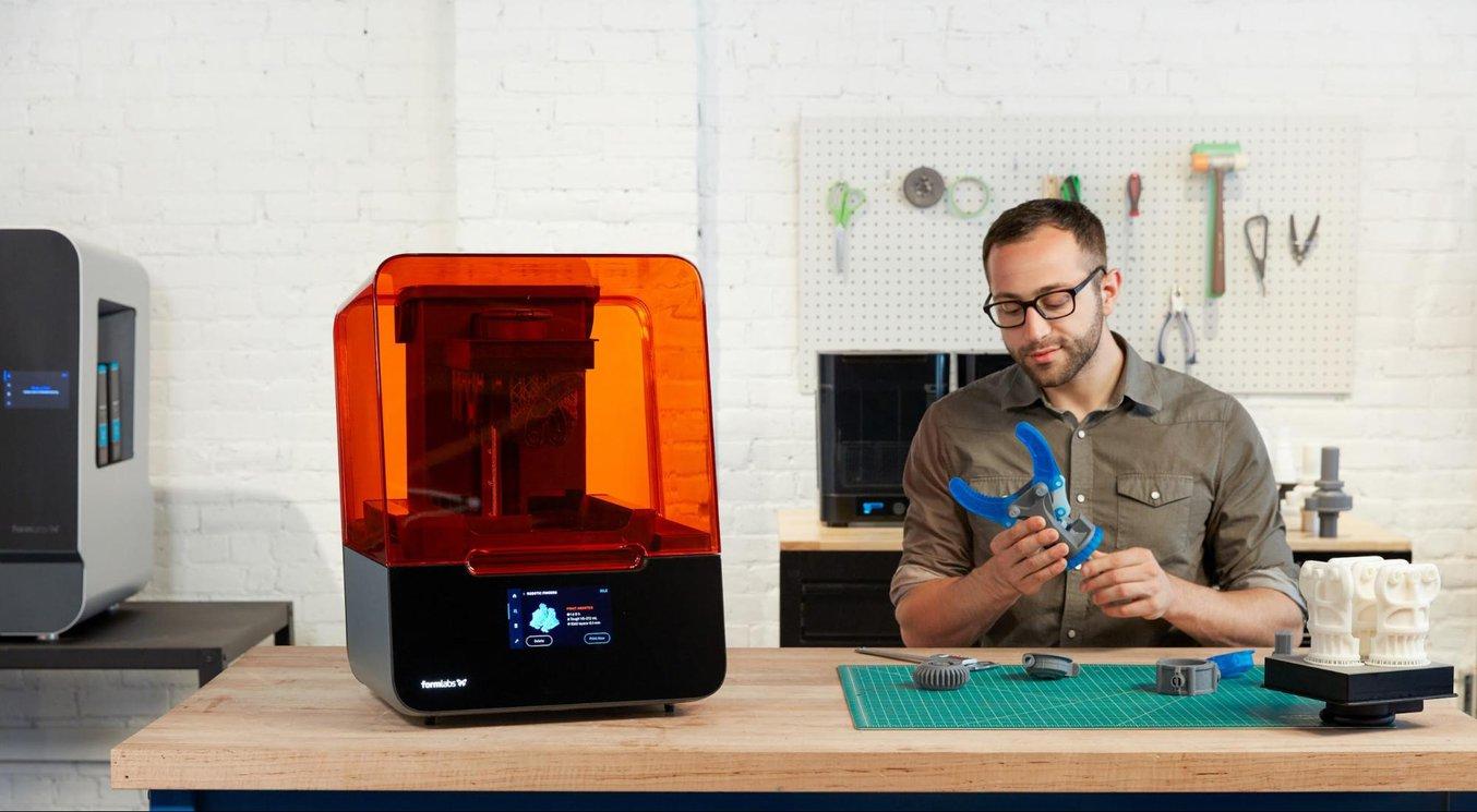 Die orangefarbene Acryl-Abdeckung der Stereolithografie-3D-Drucker von Formlabs ist unverzichtbar, da sie zur Markengeschichte gehört und zudem UV-Licht blockiert, das die Vorgänge im Drucker sonst stören würde.