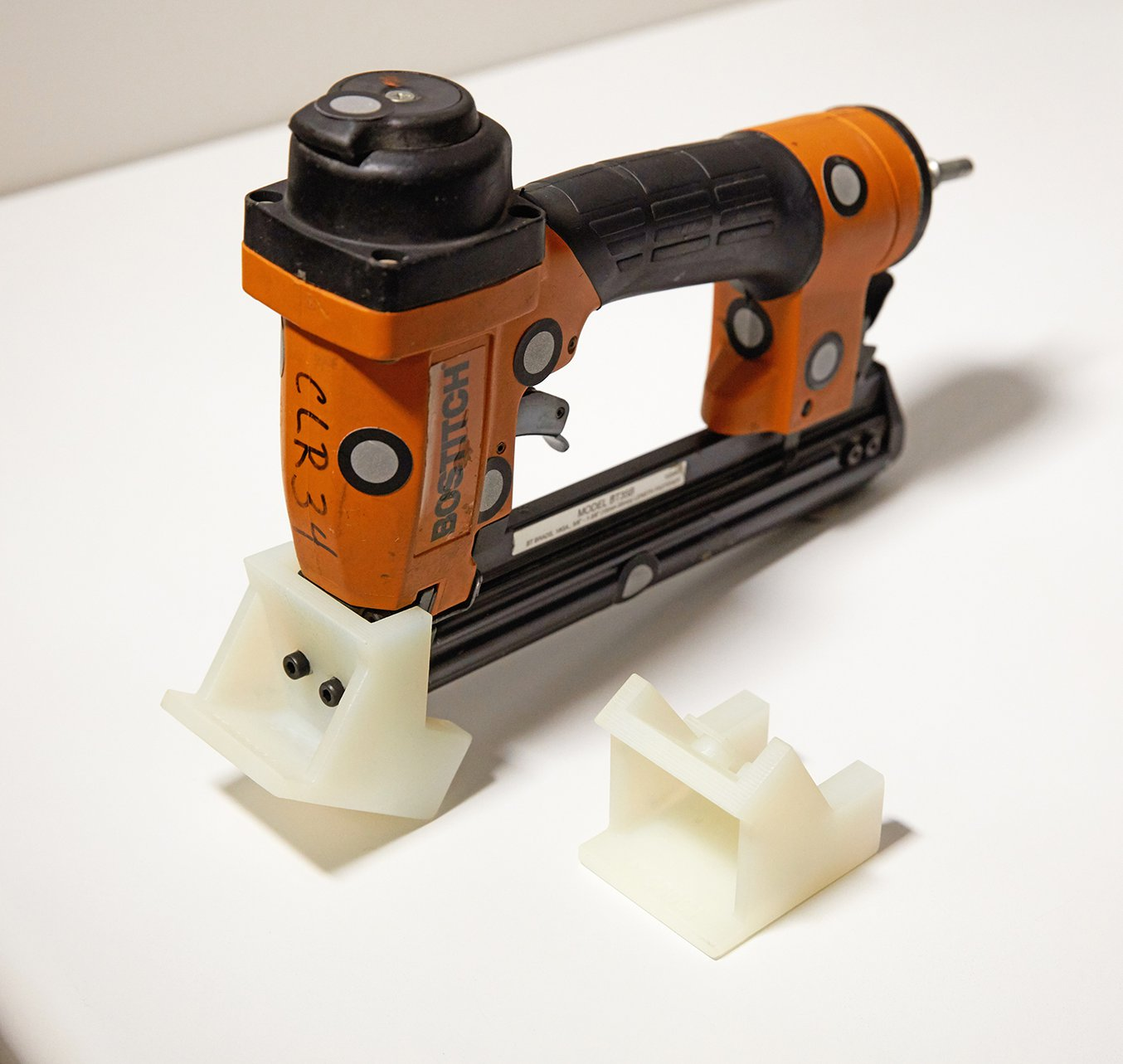 A guide for a pin tack gun 3D printed in Durable Resin.