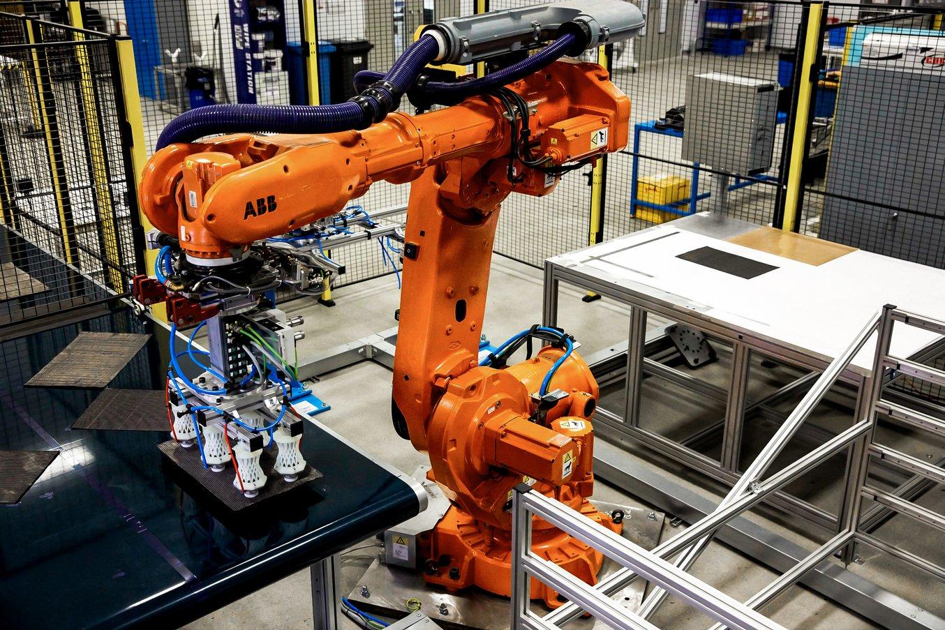 La cella robotica è progettata per automatizzare lo spostamento degli strati di composito. I fogli pretagliati entrano nella cella su un nastro trasportatore, da cui vengono prelevati tramite pinze fissate su un robot ABB a 5 assi, che sposta gli strati e
