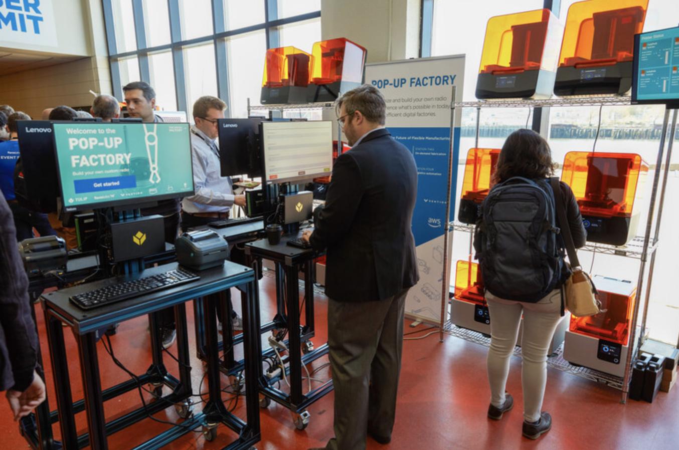 Teilnehmer konfigurieren ihre Radios an Tulip-Terminals und erstellen ihren Arbeitsauftrag, während Drucker der Typen Form 2 und Form 3 im Hintergrund laufend neue Drehknöpfe produzieren.