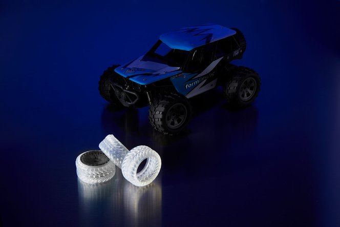 A toy RC car (right), alongside prototype tires printed in Elastic Resin (left).