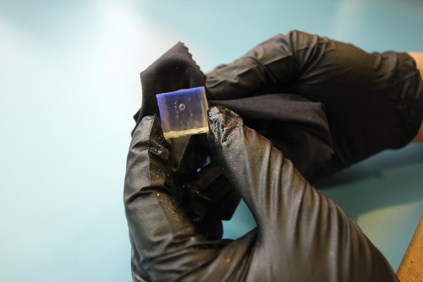 Zum Schleifen platziert das Team Schleifpapier auf einem Korkbrett mit etwas Spiel und bewegt die Linse in einem zufälligen Muster darüber, um Schleifspuren auf der Oberfläche zu vermeiden.