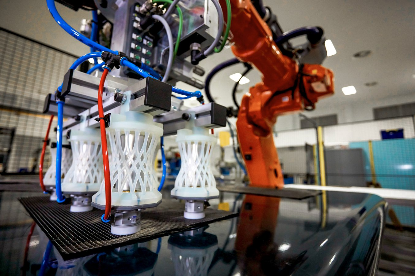 Soportes complejos que sujetan seis pinzas de un robot de coger y colocar diseñados para automatizar el desplazamiento de capas de materiales compuestos.