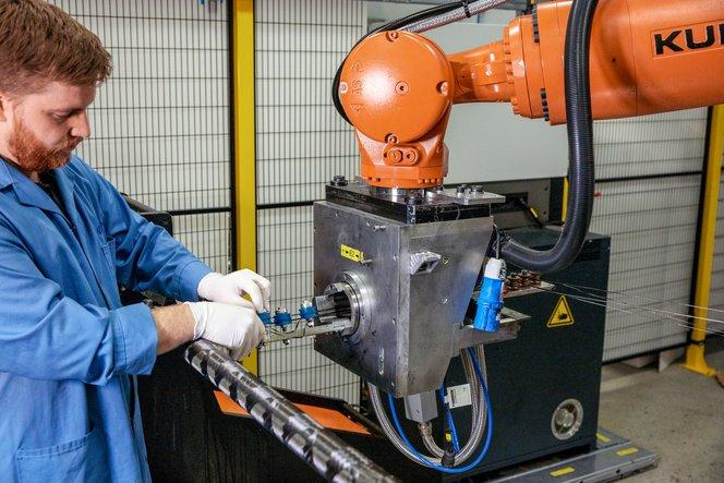 I filamenti di fibre escono dalla testina del robot e raggiungono un mandrino metallico, che viene fatto girare come un tornio. A mano a mano che la testina del robot si muove, la fibra viene depositata sopra il mandrino di filatura.