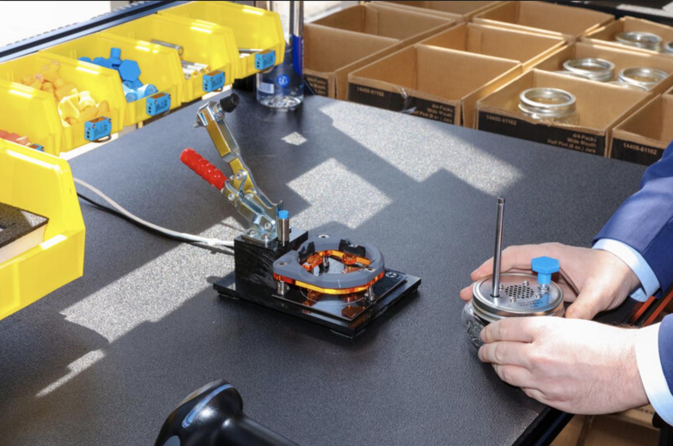 Teilnehmer montieren und programmieren Radios an Werkbänken von Vention, die mit Hardware von Tulip ausgerüstet sind. Ein großer Bildschirm zeigt schrittweise Anweisungen an und Sensoren erfassen Inventar, Zyklen und andere wichtige Fertigungsdaten.